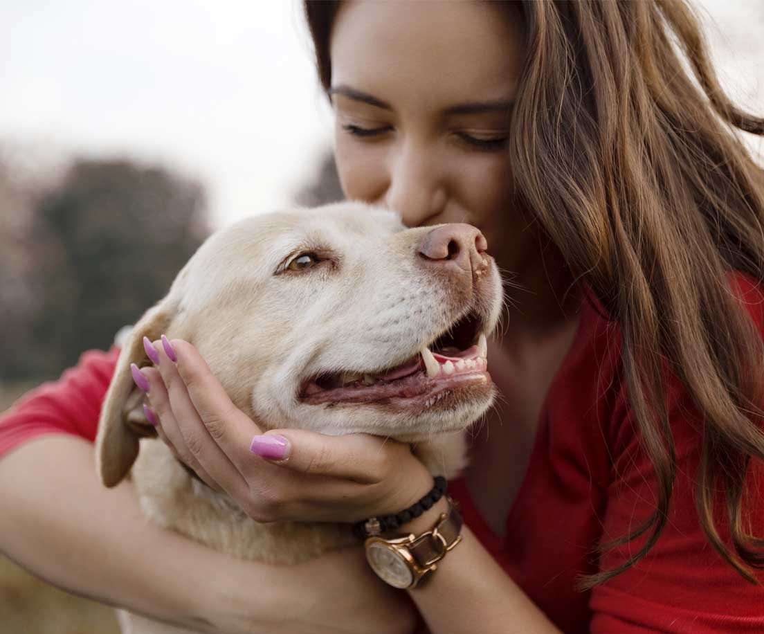 Woman hugging and kissing her dog