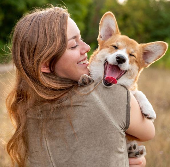 Woman holding a yawning dog